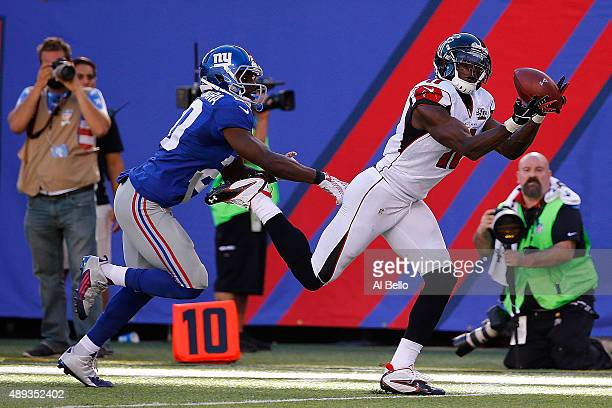Julio Jones of the Atlanta Falcons completes a first down reception in the fourth quarter under pressure from Prince Amukamara of the New York Giants...
