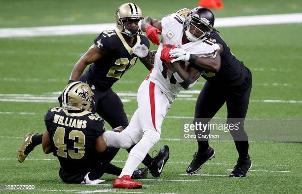 Julio Jones of the Atlanta Falcons is tackled by Demario DavisMarcus Williams and Patrick Robinson of the New Orleans Saints in the first quarter at...