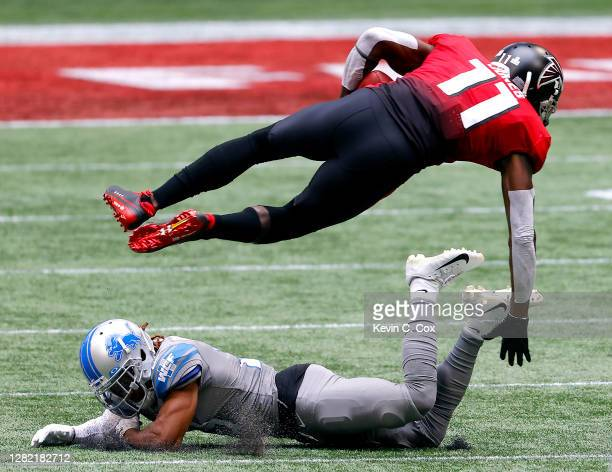 Julio Jones of the Atlanta Falcons leaps over Darryl Roberts of the Detroit Lions after making a reception during the second half at MercedesBenz...