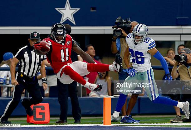 Julio Jones of the Atlanta Falcons leaps over the goal line to score a touchdown as Tyler Patmon of the Dallas Cowboys looks on the in the third...