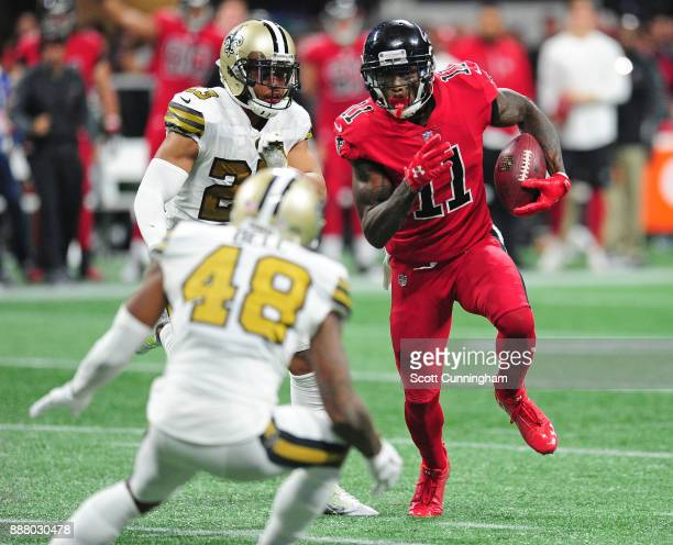 Julio Jones of the Atlanta Falcons runs with a catch against Marshon Lattimore and Vonn Bell of the New Orleans Saints at MercedesBenz Stadium on...