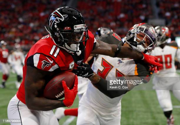 Julio Jones of the Atlanta Falcons stiff arms Carlton Davis of the Tampa Bay Buccaneers after a reception in the first half at MercedesBenz Stadium...
