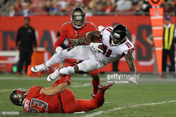Julio Jones of the Falcons makes the catch and is taken off his feet by Chris Conte and Vernon Hargreaves III of the Buccaneers during the NFL game...