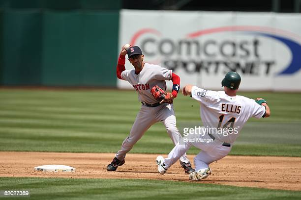 Julio Lugo of the Boston Red Sox attempts to complete a double play as Mark Ellis of the Oakland Athletics slides into second base during the game at...