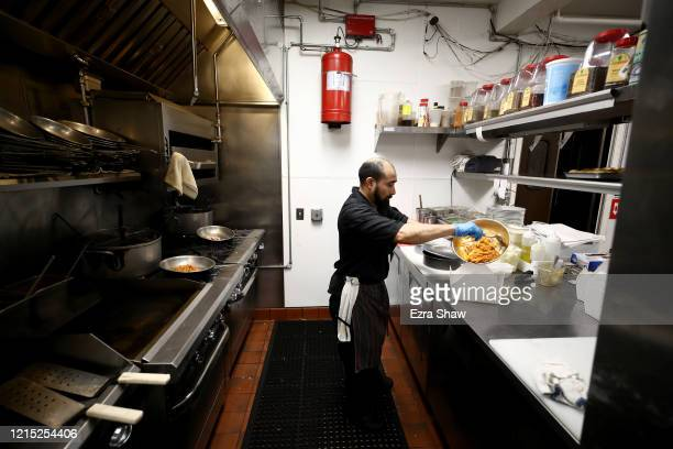 Julio Mis the executive sous chef at Sociale prepares dinners for delivery and curbside pickup in the kitchen with a reduced staff on March 27 2020...
