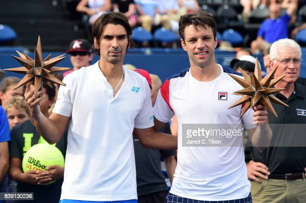 Julio Peralta of Chile and Horacio Zeballos of Argentina pose with their finalist's trophies after their finals match against JeanJulien Rojer of...