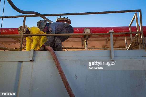 Julio Perez left and Gene Starbuck right both floor hands work to connect a large tube on the Raven Oil Drilling rig near Watford City ND Oct 1 2013...