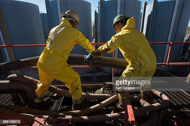 Julio Perez left and Pedro Michel right both floor hands work at connecting tubes on the Raven Oil Drilling rig near Watford City ND Oct 1 2013 In...