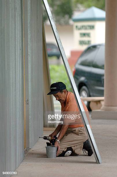 Julio Rojas gets ready to install the last panel of the hurricane shutters he put up in a Plantation Florida shopping center Thursday August 25 2005...