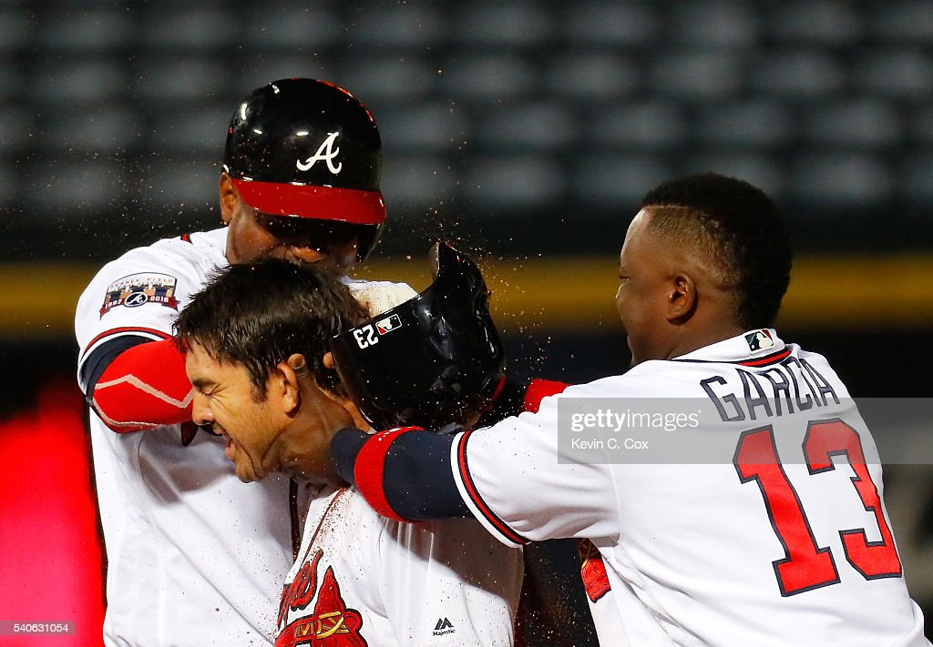 Julio Teheran #49 and Adonis Garcia #13 of the Atlanta Braves toss dirt on Chase d'Arnaud #23 after he hit a walk-off single to give the Braves a 9-8 win over over the Cincinnati Reds in the 13th inning at Turner Field on June 15, 2016 in Atlanta, Georgia.