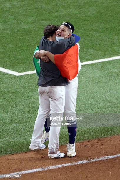Julio Urías of the Los Angeles Dodgers celebrates with Enrique Hernandez after defeating the Tampa Bay Rays 31 in Game Six to win the 2020 MLB World...