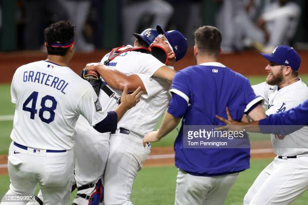 Julio Urias and Austin Barnes of the Los Angeles Dodgers celebrates after defeating the Tampa Bay Rays 3-1 in Game Six to win the 2020 MLB World...