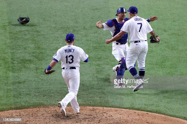 Julio Urias of the Los Angeles Dodgers celebrates with Austin Barnes after defeating the Tampa Bay Rays 31 in Game Six to win the 2020 MLB World...