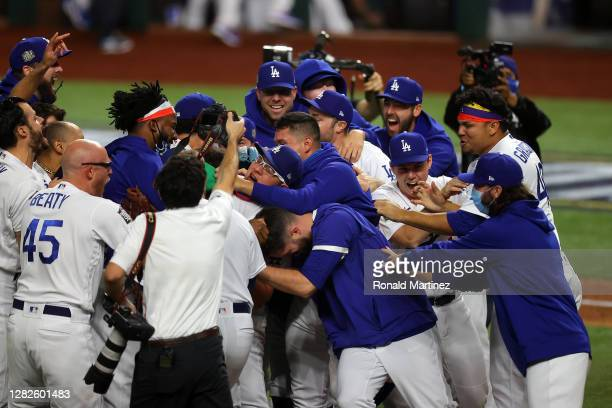 Julio Urias of the Los Angeles Dodgers is congratulated by his teammates after defeating the Tampa Bay Rays 3-1 in Game Six to win the 2020 MLB World...