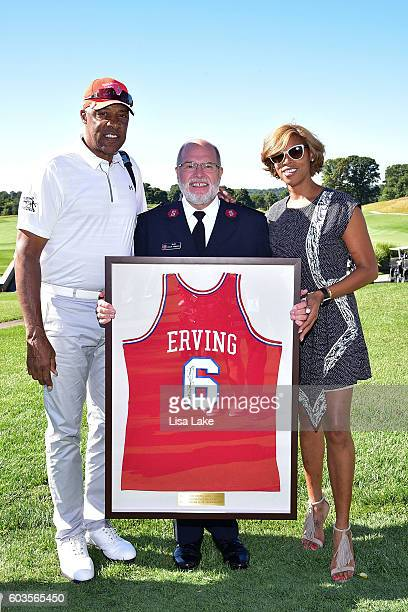 Julius and Jazmin Erving present Director of Operations of The Salvation Army Major A Phillip Ferreira with a signed framed Julius Erving jersey...