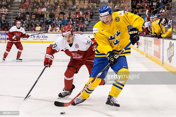 Julius Bergman of Sweden moves the puck against Emil Rasmussen of Denmark during the 2015 IIHF World Junior Championship on December 27 2014 at the...