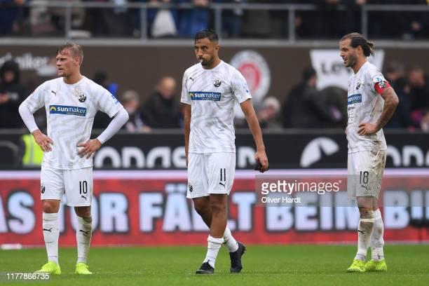 Julius Biada, Aziz Bouhaddouz and Dennis Diekmeier of SV Sandhausen looks dejected after the Second Bundesliga match between FC St. Pauli and SV...