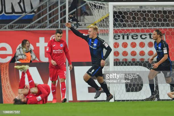 Julius Dueker and Tobias Schwede of Paderborn celebrate their teams second goal while Patrick Weihrauch and Jonathan Clauss of Bielefeld look...