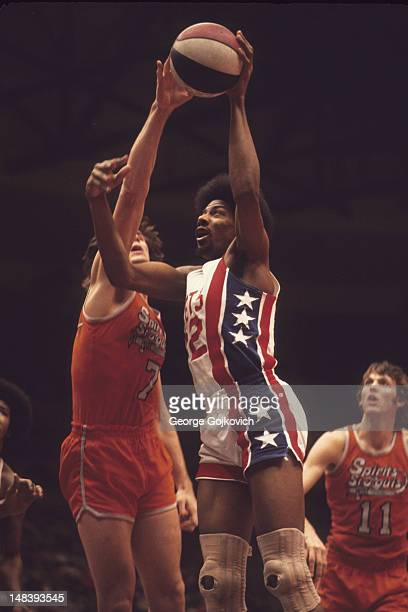 Julius Erving of the New York Nets shoots against Terry Driscoll of the Spirits of St Louis as Gus Girard looks on during an American Basketball...