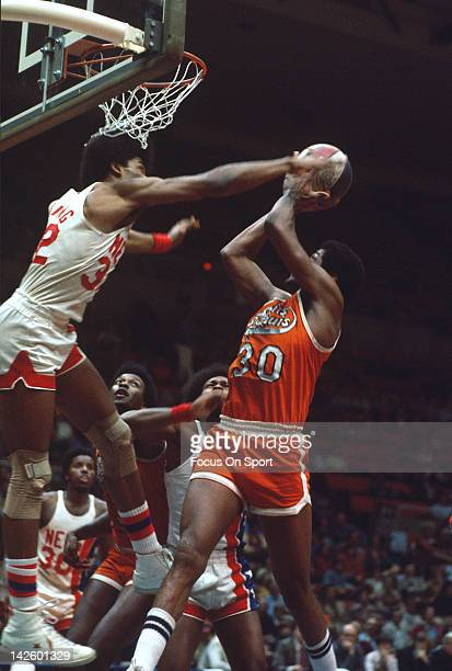 Julius Erving of the New Jersey Nets blocks the shot of ML Carr of the St Louis Spirits during an ABA basketball game circa 1975 at the Rutgers...
