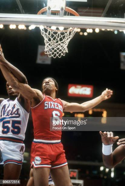 Julius Erving of the Philadelphia 76ers battles for a rebound with Albert King of the New Jersey Nets during an NBA basketball game circa 1982 at the...