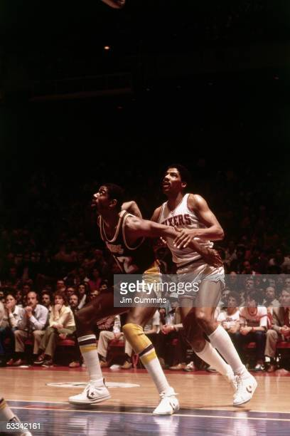 Julius Erving of the Philadelphia 76ers battles for rebound position against Magic Johnson of the Los Angeles Lakers during an NBA game circa 1980 at...