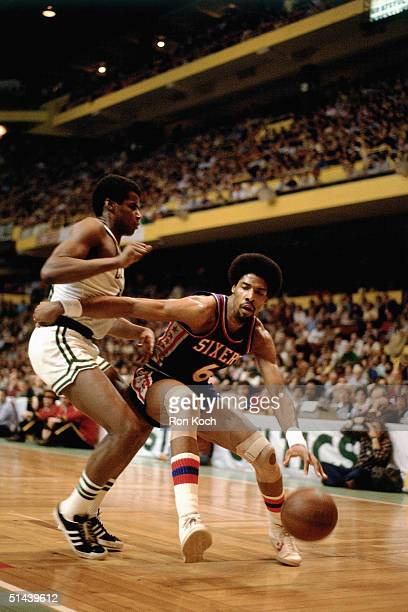 Julius Erving of the Philadelphia 76ers drives to the basket against Robert Parish of the Boston Celtics during an NBA game in 1985 at the Boston...