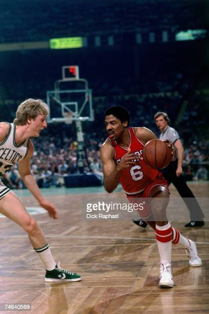 Julius Erving of the Philadelphia 76ers drives to the basket against Larry Bird of the Boston Celtics during a 1980 NBA game at the Boston Garden in...