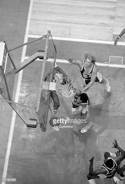 """Julius Erving of the Philadelphia 76ers drives to the basket in what becomes known as """"The Move"""" against Mark Landsberger and Kareem Abdul-Jabbar of..."""
