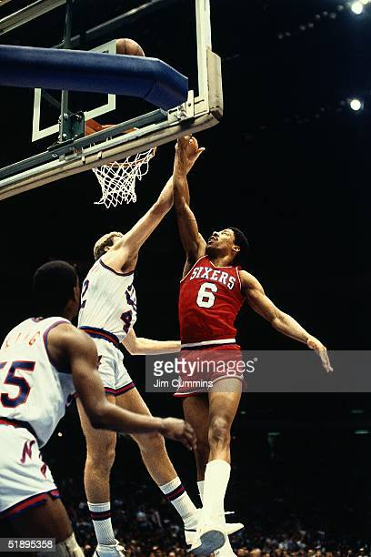 Julius Erving of the Philadelphia 76ers goes up for a layup against the New Jersey Nets during an NBA game in 1983 at The Brendan Byrne Arena in East...
