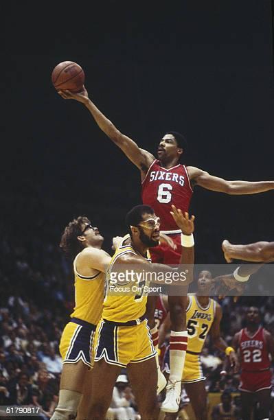 Julius Erving of the Philadelphia 76ers jumps to shoot over Los Angeles Lakers forward Kurt Rambis and Kareem AbdulJabbar