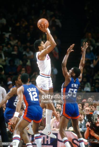 Julius Erving of the Philadelphia 76ers shoots over Albert King of the New Jersey Nets during an NBA basketball game circa 1982 at The Spectrum in...