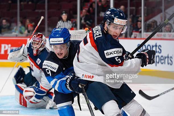 Julius Honka of Team Finland holds onto Marco Hochel of Team Slovakia during the 2015 IIHF World Junior Hockey Championship game at the Bell Centre...