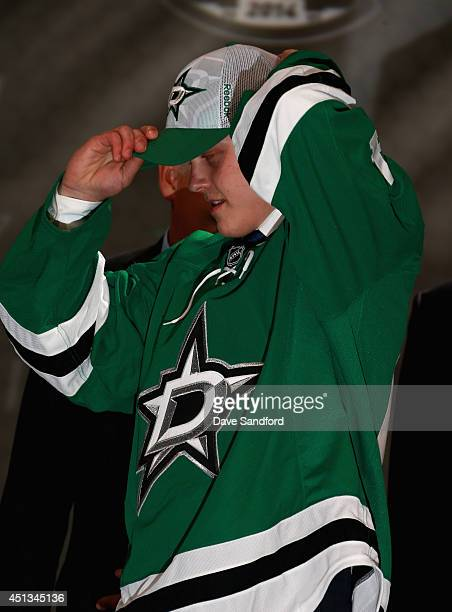 Julius Honka puts on his hat after being selected 14th overall by the Dallas Stars during the 2014 NHL Entry Draft at Wells Fargo Center on June 27...