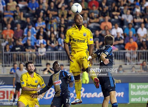 Julius James of the Columbus Crew heads the ball away from the goal in front of teammate Danny O'Rourke as well as Freddy Adu and Antoine Hoppenot of...