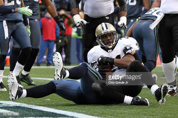 Julius Jones of the New Orleans Saints looks up after his fiveyard touchdown run as he is tackled in the endzone by Will Herring of the Seattle...