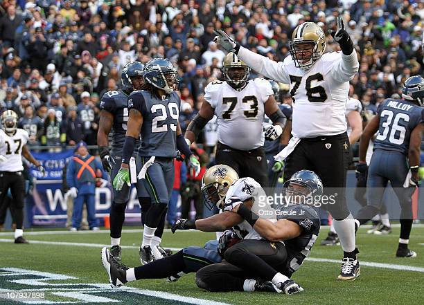 Julius Jones of the New Orleans Saints scores on a fiveyard touchdown run as he is tackled in the endzone by Will Herring of the Seattle Seahawks as...
