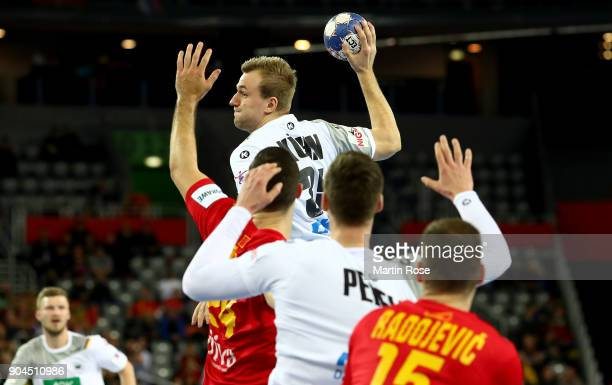 Julius Kuehn of Germany challenges Milos Bozovic of Montenegro during the Men's Handball European Championship Group C match between Germany and...