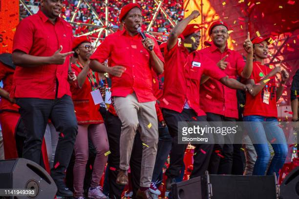 Julius Malema, leader of the Economic Freedom Fighters , center, sings on stage during an Economic Freedom Fighters party campaign rally in Soweto,...