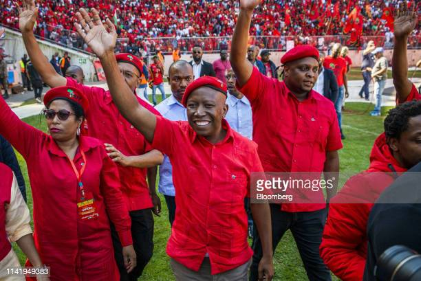 Julius Malema, leader of the Economic Freedom Fighters , center, waves to the crowd during an Economic Freedom Fighters party campaign rally in...