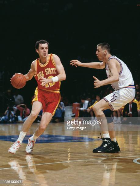 Julius Michalik, Guard for the Iowa State Cyclones dribbles the ball down court past Greg Ostertag of the University of Kansas Jayhawks during the...