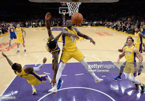 Julius Randle of the Los Angeles Lakers blocks a layup by Jordan Bell of the Golden State Warriors with Kentavious CaldwellPope of the Los Angeles...