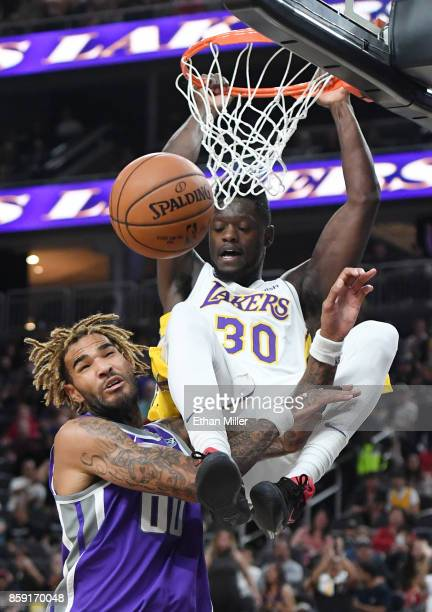 Julius Randle of the Los Angeles Lakers dunks against Willie CauleyStein of the Sacramento Kings during their preseason game at TMobile Arena on...