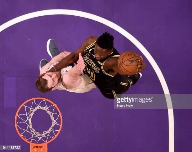 Julius Randle of the Los Angeles Lakers dunks over Tyler Zeller of the Milwaukee Bucks during the first half at Staples Center on March 30 2018 in...