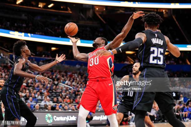 Julius Randle of the New Orlean Pelicans grabs a rebound over Jonathan Isaac Evan Fournier and Wes Iwundu of the Orlando Magic during the game at the...