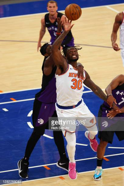 Julius Randle of the New York Knicks battles Pascal Siakam of the Toronto Raptors for a rebound at Madison Square Garden on April 11, 2021 in New...