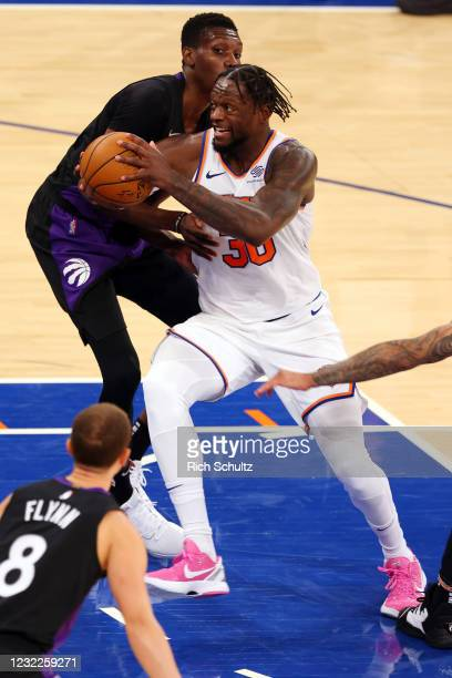 Julius Randle of the New York Knicks drives to the basket as Chris Boucher of the Toronto Raptors defends at Madison Square Garden on April 11, 2021...