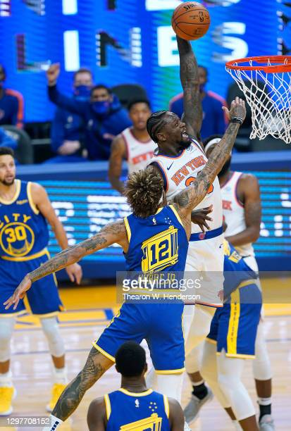 Julius Randle of the New York Knicks goes up to attempt a slam dunk over Kelly Oubre Jr. #12 of the Golden State Warriors during the first half of an...