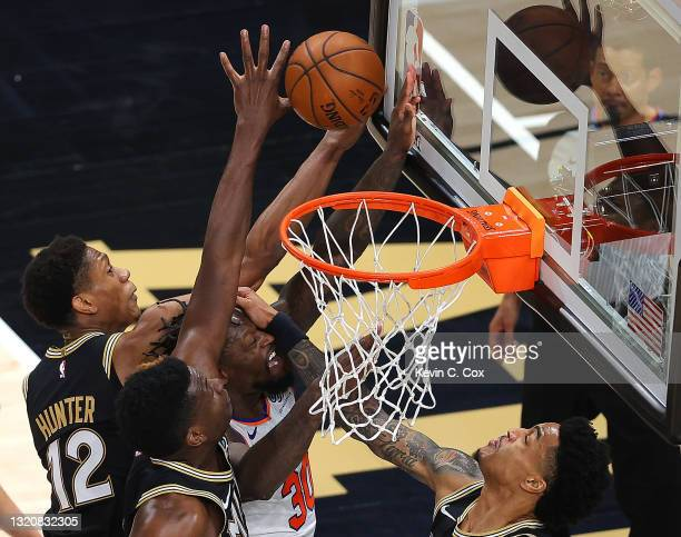 Julius Randle of the New York Knicks has the ball knocked away as he is defended by De'Andre Hunter, Clint Capela and John Collins of the Atlanta...