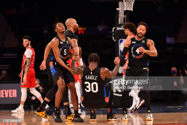 Julius Randle of the New York Knicks is helped up by teammates Immanuel Quickley of the New York Knicks and Derrick Rose of the New York Knicks...